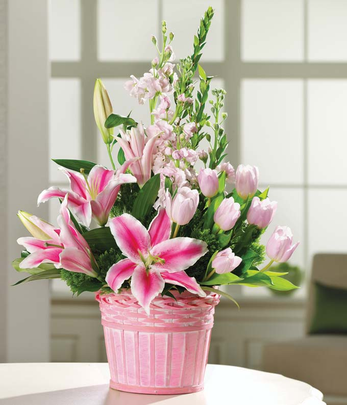 pink tulips and pink lilies in a pink basket