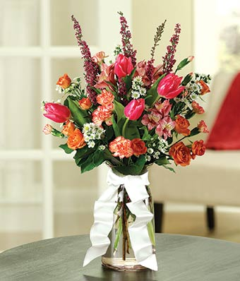Pink tulips, carnations and orange spray roses in sympathy gift