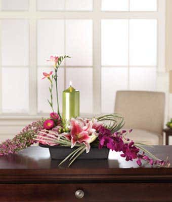 Pink lilies, asters and purple orchids with candle in arrangement