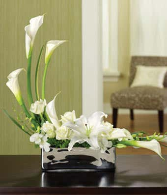 White calla lilies, white roses and white orchids in silver vase