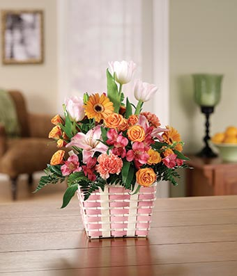 Pink tulips,pink alstroemeria and orange daisies in a basket