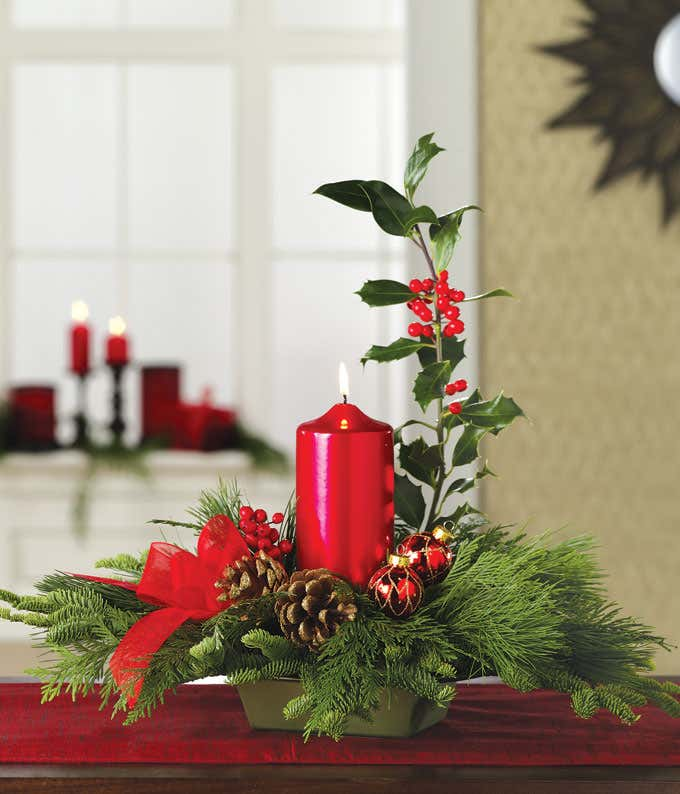Large red candle in the center of a white pine centerpiece