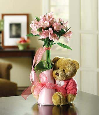 teddy bear with pink flowers in a bud vase