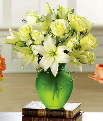 White roses and white lilies in green vase