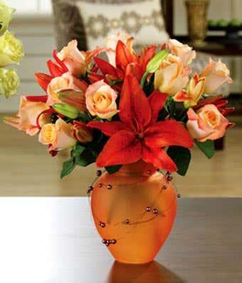 Orange lilies and orange roses in tangerine vase