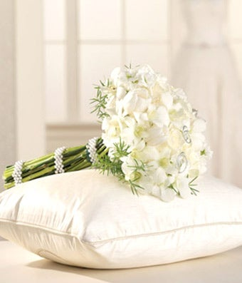 White roses, white tulips and orchids arranged in a bridesmaid bouquet