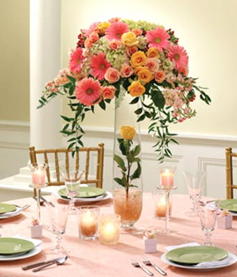 Pink gerbera daiseis and orange roses in a floral centerpiece