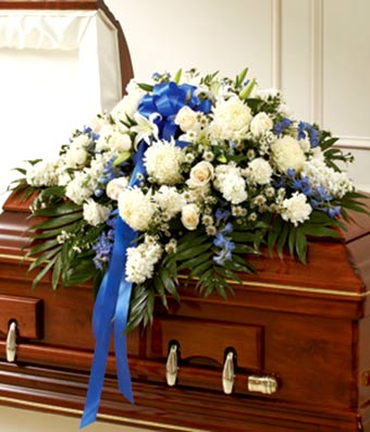 White roses and blue delphinium floral casket cover
