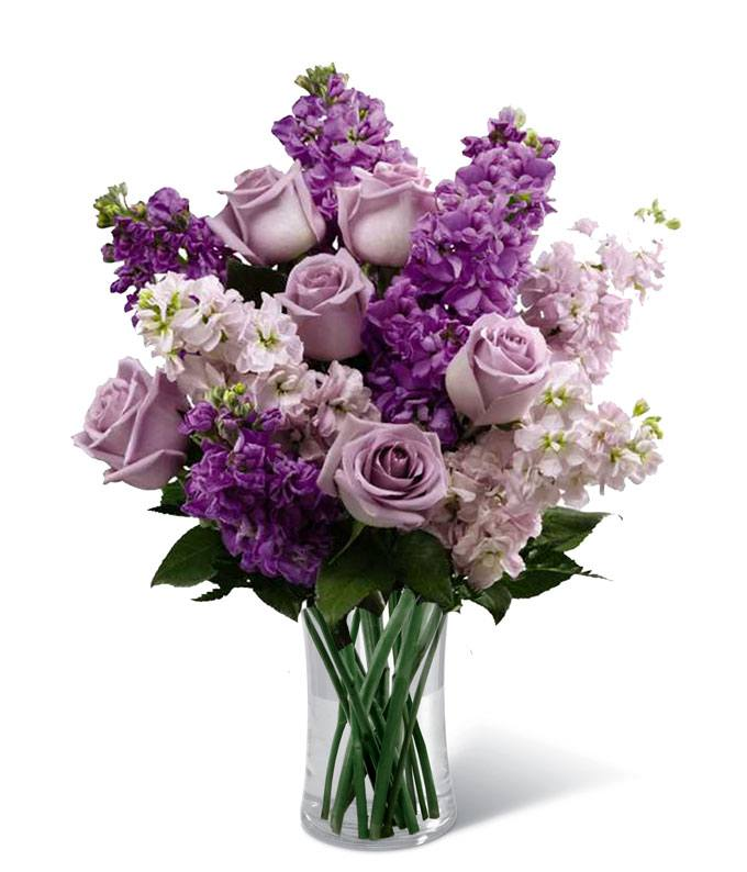 Purple roses and stock in glass vase