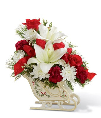 Red and white flowers delivered in a sleigh vase