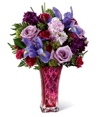 Flowers - The Early Spring Garden - Regular Celebrate the beauty of early Spring mornings, with this stunning floral bouquet. The Early Spring Garden arrangement is filled with bright colors including purple roses, Iris as well as red floral tones. Delivered in a unique, colorful vase this arrangement is ideal for sending to someone you love. Includes: • Purple Roses • Irises • Seasonal Greens • Colorful Vase