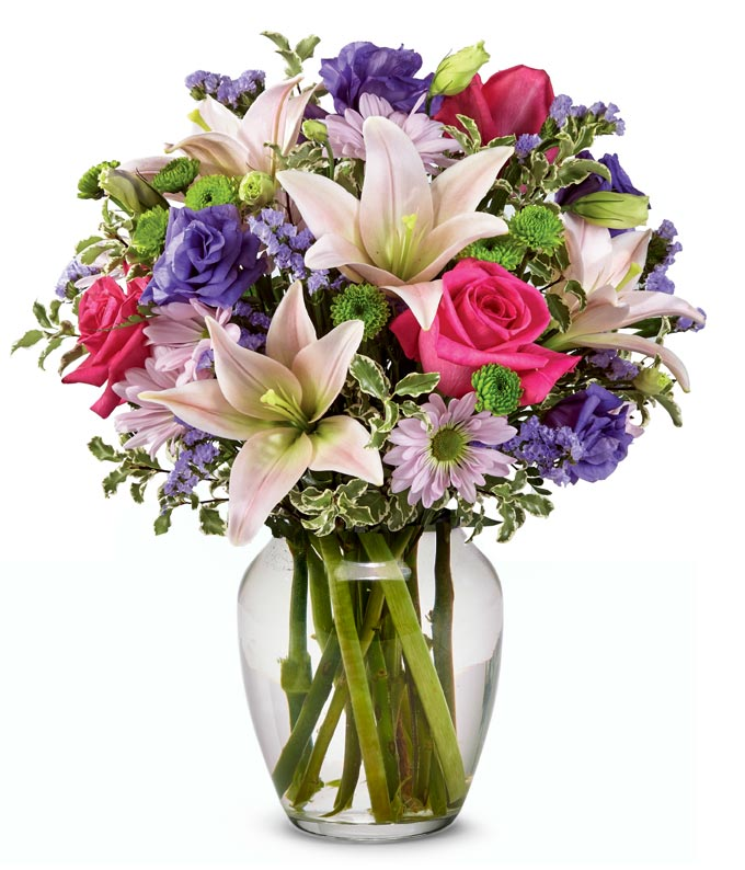 Pink Asiatic lilies, pink roses and purple flowers in a vase