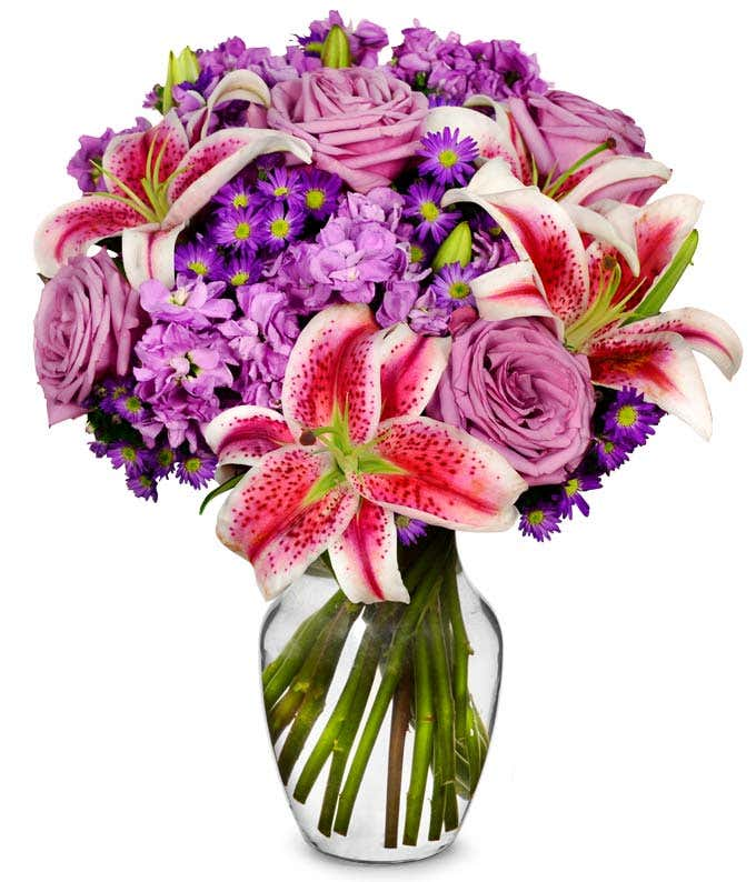 Purple roses, pink stargazer lilies and purple filler flowers in a vase
