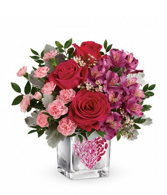 Square vase with heart decoration is filled with red roses, light pink carnations and purple alstroemeria