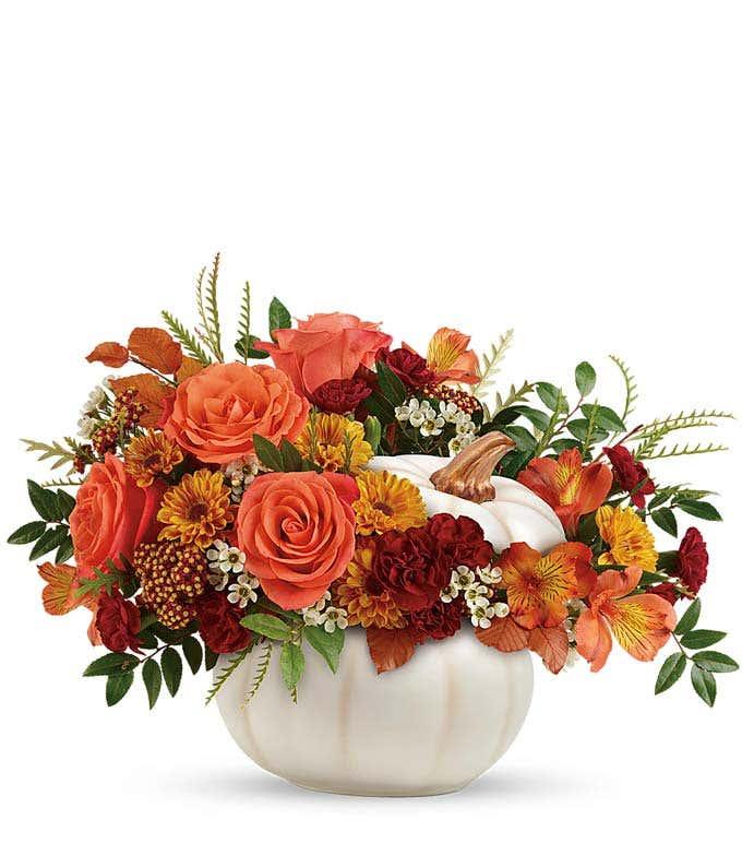 Orange Fall flowers arranged in a white pumpkin