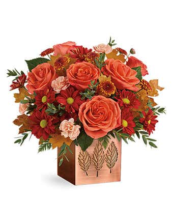 A Bronze planter is filled with orange roses and peach mini carnations