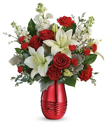 White lilies, red roses and red carnations in tall red valentine vase