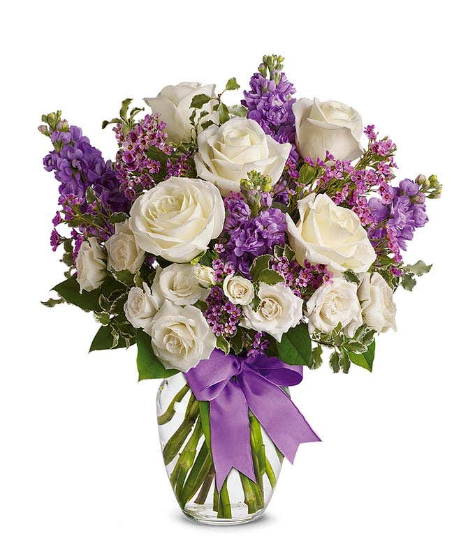 White roses and purple stock in a vase