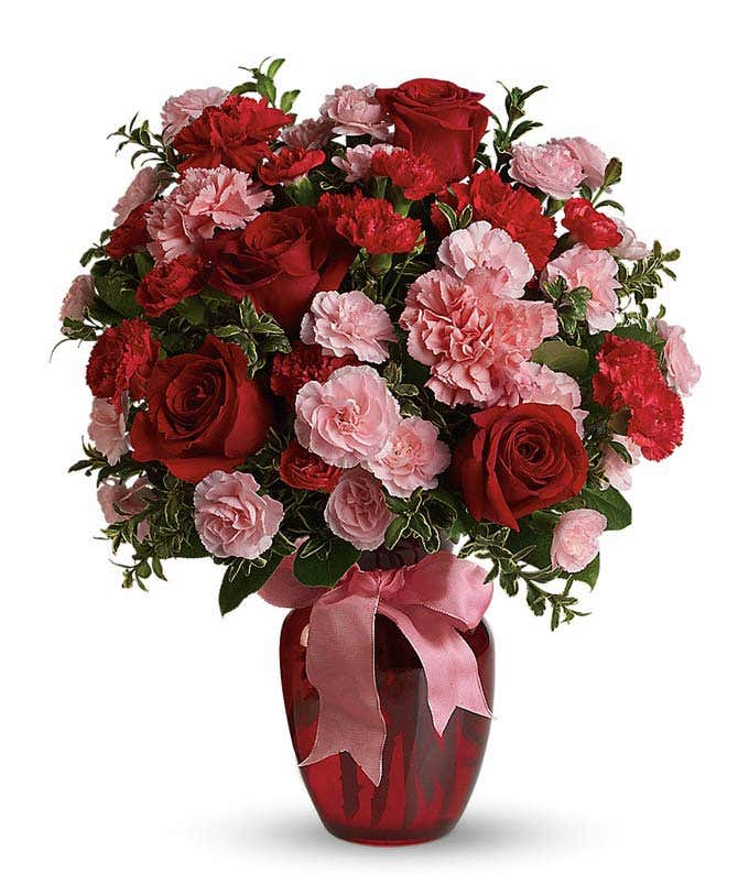 Red roses, pink carnations in a red vase for a romantic bouquet