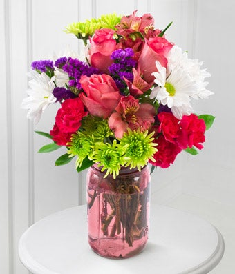 Mason jar is delivered with pink roses, pink Peruvian lilies and white daisies