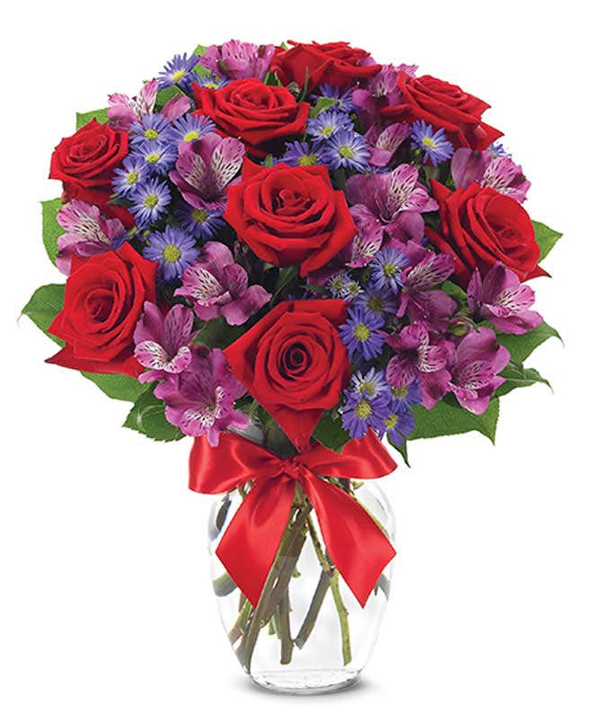 Red roses arranged with purple alstroemeria and monte casino.
