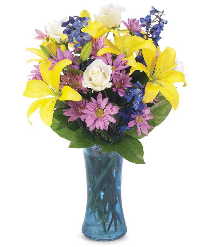 Yellow lilies and purple daisies in a colorful vase