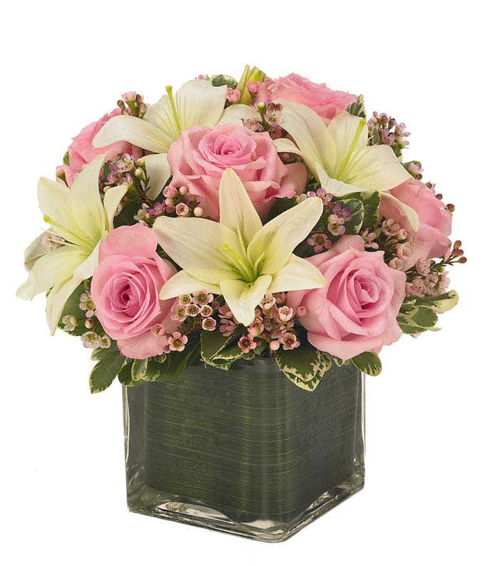 Light pink roses, white lilies and pink waxflower in square vase