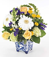 White flowers and yellow roses in white ceramic container
