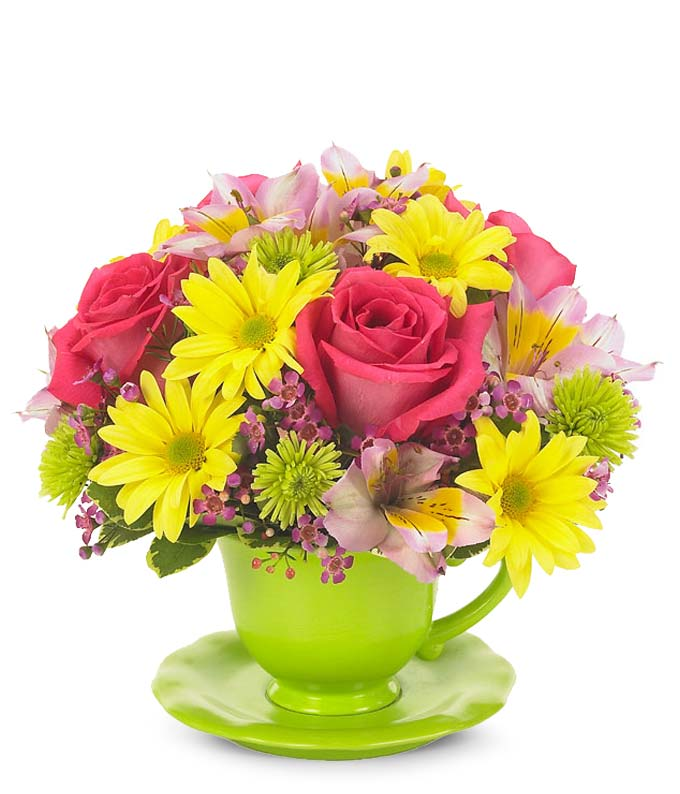 Hot pink roses, yellow daisies and green poms in a teacup vase
