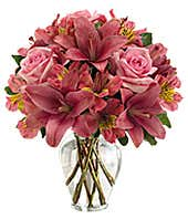 Pink roses, lilies and alstroemeria in clear vase