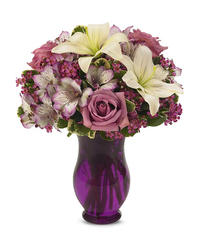 Purple roses, white lilies and purple astroemeria delivered by a florist