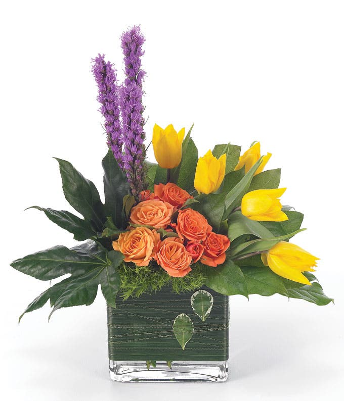 Yellow tulips and orange roses in square vase