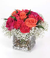 Red roses and orange roses in square glass vase