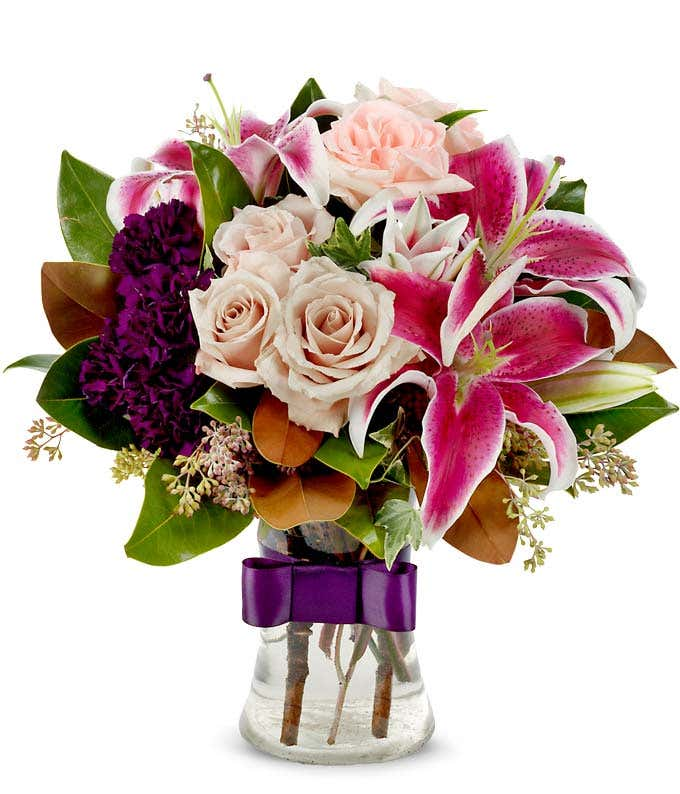 Pink stargazer lilies, cream roses and purple carnation bouquet