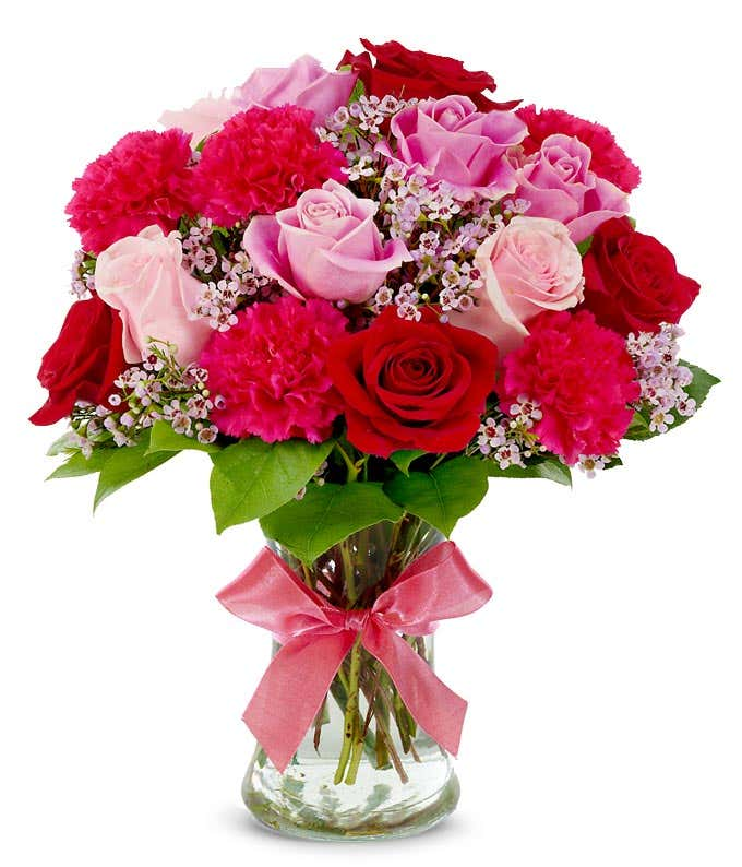 Pink roses, red roses and pink carnations in glass vase
