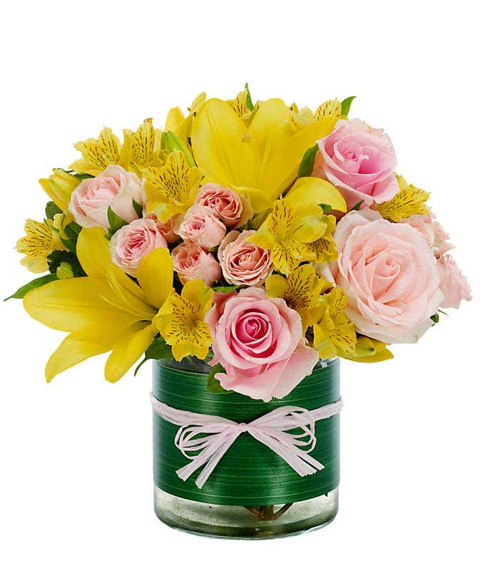 Yellow asiatic lilies, pink roses and yellow alstroemeria in circular vase
