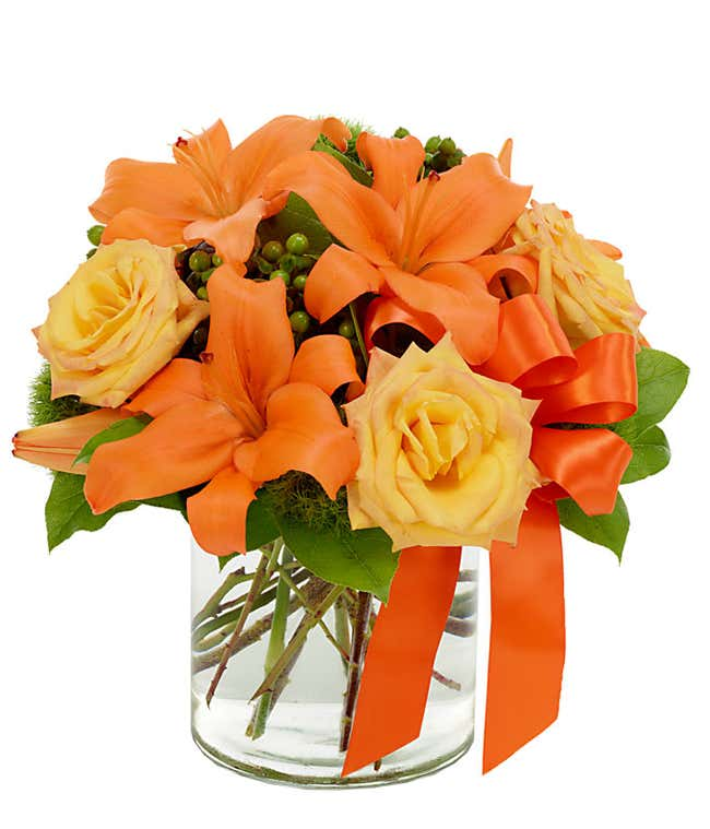 Orange asiatic lilies, yellow roses and green hypericum in circular vase