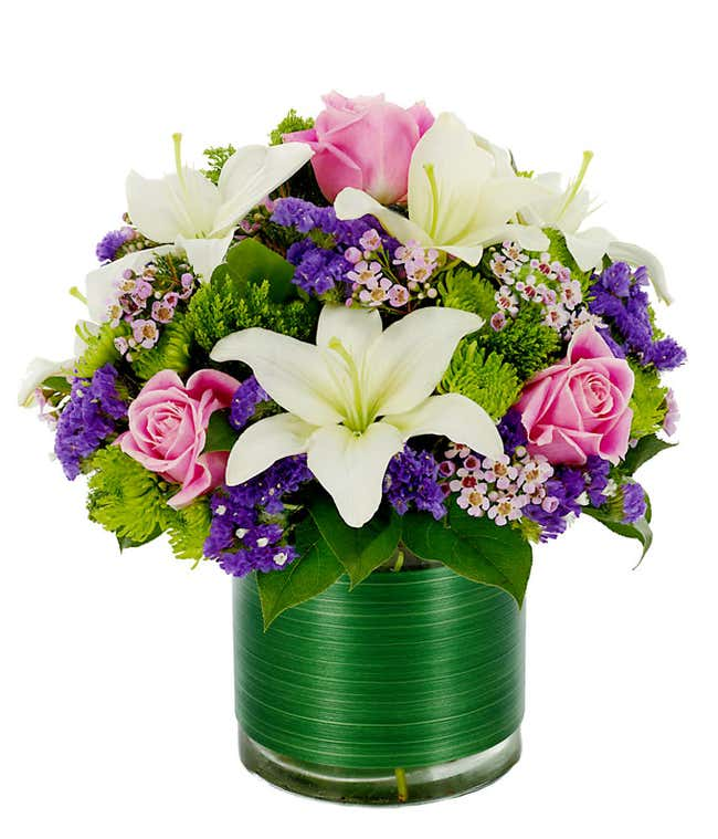 White asiatic lilies, purple statice and green poms in a circular glass vase