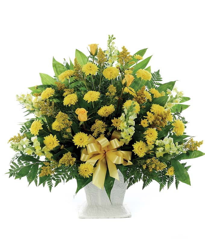 Yellow snapdragons and mums in a funeral flower arrangement