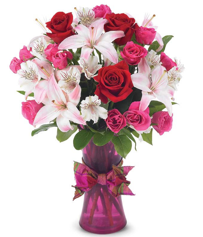 Red roses, pink lilies and pink spray roses in purple vase for Valentines Day