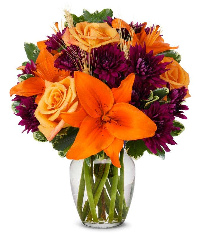 Flower arrangement with orange lilies, orange roses and purple flowers