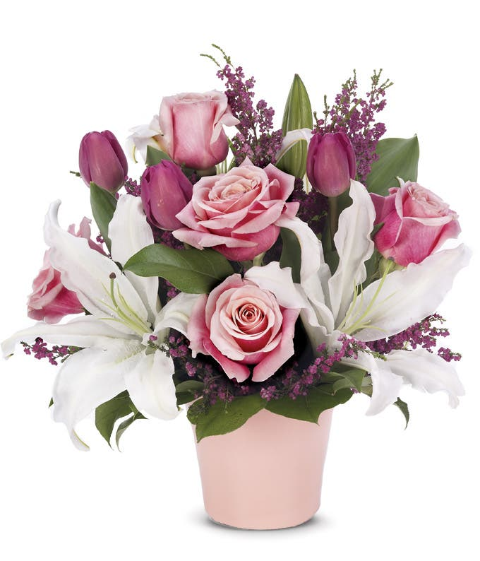 Pink roses, white lilies and colorful tulips in pink cache pot