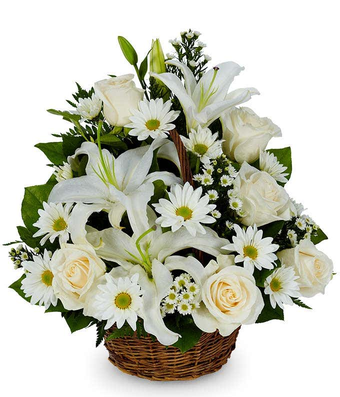 White lilies, white roses and white daisies in a basket