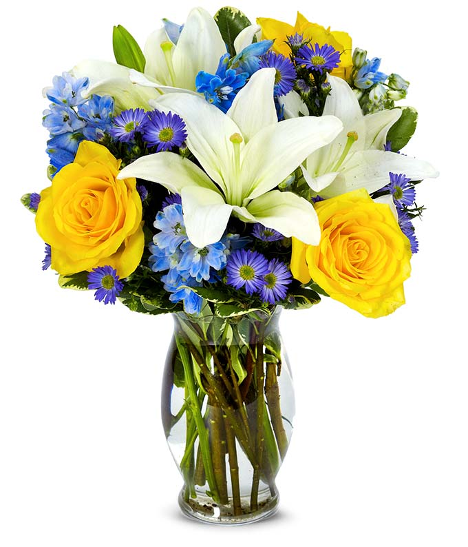 Yellow roses, blue delphinium and white lilies in a vase