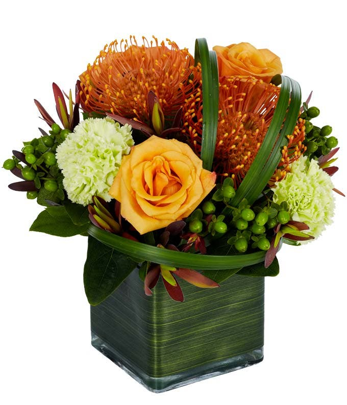 Orange roses, orange spider mums and green carnations in a modern square vase