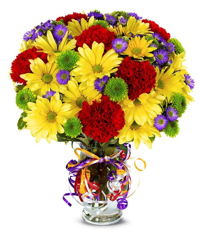 Yellow daisies, red carnations and green button pops in a glass vase