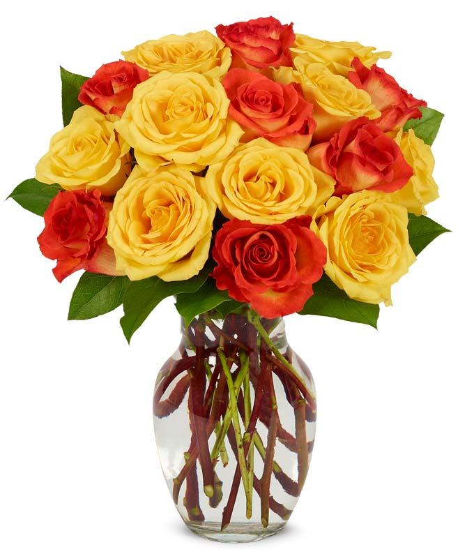Yellow rose and orange roses in a glass vase