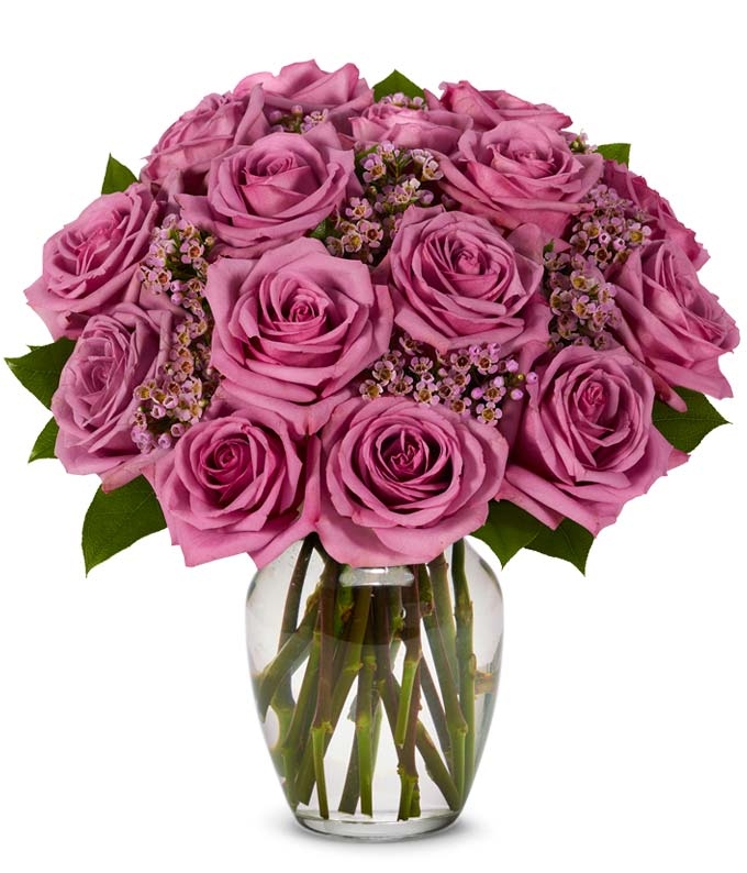 Purple rose arrangement with purple decoration in a glass vase