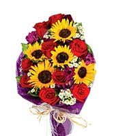 Sunflowers, red roses and purple alstroemeria in hand tied bouquet