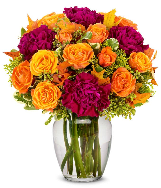 Deep purple carnations arranged with orange spray roses